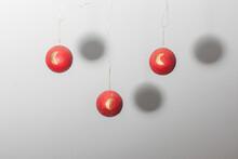 3 Bolas Rojas De Decoración Navideñas Suspendidas En El Aire Con Lunas Doradas Estampadas Y Sombra Circular Proyectada En La Pared