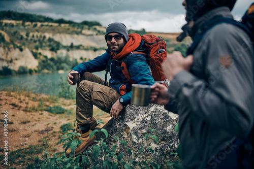 Two men in nature taking a break from hiking Fotobehang