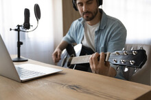 Crop Close Up Of Millennial Male Singer Hold Play Guitar Have Online Video Lesson On Laptop At Home Studio. Young Man Artist Or Composer Compose Music Single Or Song Using Instrument. Hobby Concept.