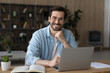 Portrait of smiling millennial Caucasian male employee in glasses sit at desk at home office working distant on laptop. Happy young 20s man in spectacles use computer, consult client customer online.