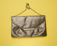 Rectangular Golden Leather Fashion Clutch On A Metal Chain On A Yellow Background