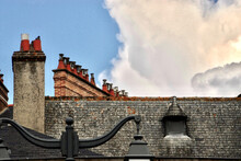 Shingled Roof With Stone And Clay Chimneys, Roof Window And Street Lantern Against Blue Sky With Big White Stormy Cloud