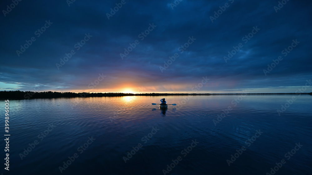 Fototapeta Distant kayaker at sunset on Coot Bay in Everglades National Park, Florida under winter cloudscape reflected in tranquil water.