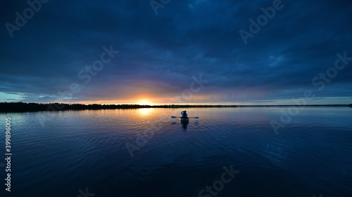 Obraz Distant kayaker at sunset on Coot Bay in Everglades National Park, Florida under winter cloudscape reflected in tranquil water. - fototapety do salonu