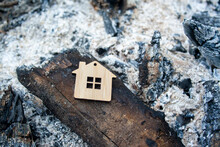 Fire Concept. The House Burned Down. Mortgage Symbol. Realtor Real Estate Loan Concept. The Figure Of The House Lies On The Coals And Ashes.