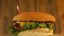 Delicious Burger With Small Austrian Flag On Top Of Them With Toothpicks. Yummy Hamburger Rotating.