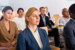 Portrait of focused female entrepreneur sitting with group of people in conference room during business event