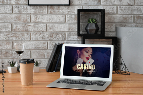 Cuadros en Lienzo Text CASINO ONLINE on screen of laptop on table in room