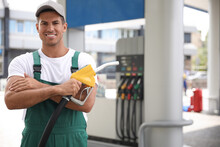 Worker With Fuel Pump Nozzle At Modern Gas Station