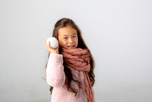 Little Asian Girl Holding A Snowball On A White Background