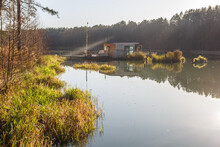 Landing Stage House On Wooden Pier In Water In Forest In Evening