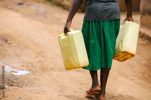 Fototapeta Woman carrying water in Uganda, Africa