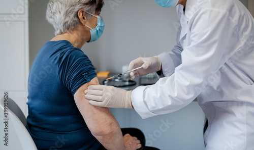 Leinwand Poster Senior woman being vaccinated against coronavirus by a female doctor