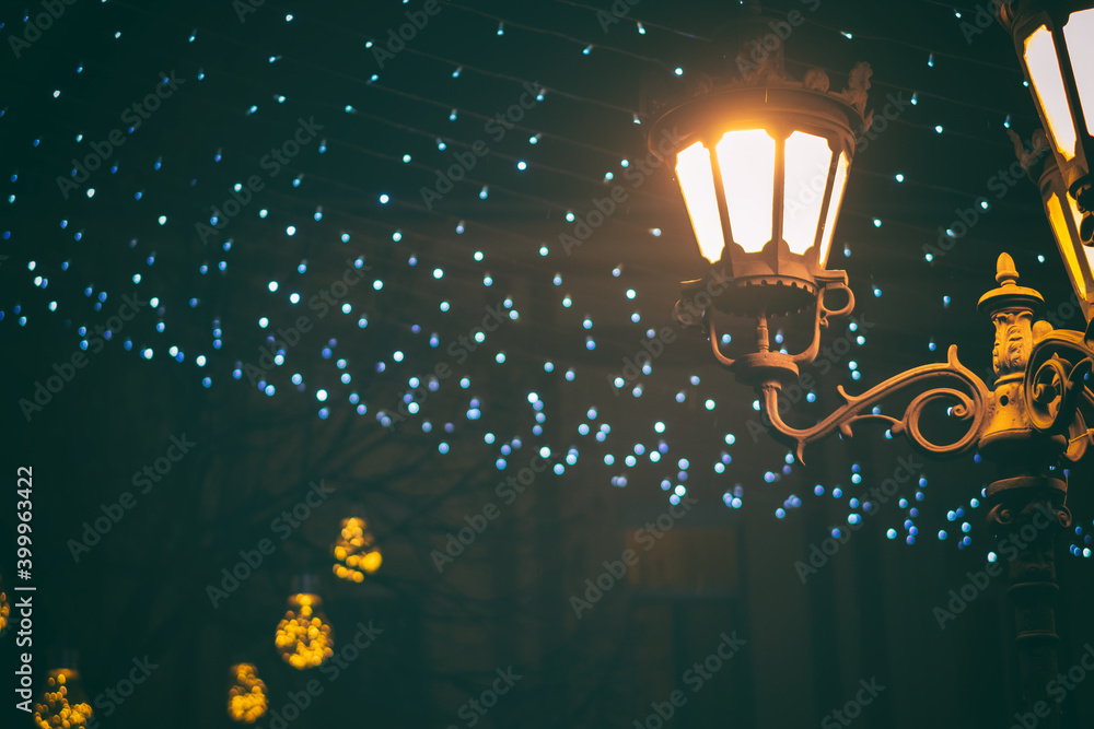 Fototapeta Night urban landscape, city street lamp on the background of festive illumination and city lighting