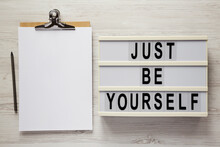 'Just Be Yourself' On A Lightbox, Clipboard With Blank Sheet Of Paper On A White Wooden Background, Top View. Flat Lay, Overhead, From Above.