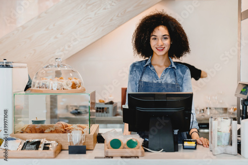 Fototapeta Confident young smiling african waitress standing at cafe counter in small cafeteria obraz