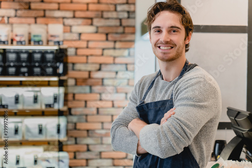 Fototapeta Confident caucasian young barista standing with his arms crossed in small coffee shop obraz