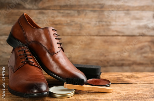 Fototapeta Shoe care products and footwear on wooden table. Space for text