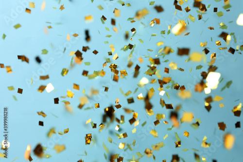 Carta da parati Shiny golden confetti falling down on light blue background