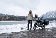 Female Motorcyclist Standing With Her Motorcycle Near Snowy Mountain River, Snow Peaks Skyline View