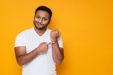 Asian Young Disappointed Man Gesturing At His Arm As Late Time
