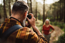 Senior Man Taking Photo With Camera Of Woman In Forest