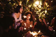 Group Of Friends Cheering With Sparklers On Party Together