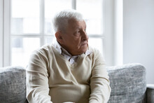 Lost In Memories. Sad Thoughtful Retired Grey Haired Man Sit On Soft Couch At Home Spend Time On His Own. Serious Pensive Mature Male Pensioner Relaxing Indoors Looking Aside Feeling Lonely Nostalgic