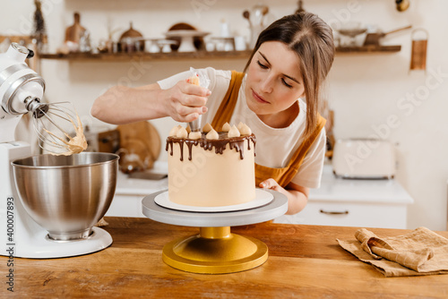 Fototapeta Beautiful focused pastry chef woman making cake with cream