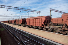 Grain Carrier Freight Car For Transportation Of Bulk Cargo Of Grain Crops, Railway Track With Rails And Wagons Going Into Perspective, Background On Theme Of Transportation And Export Of Grain Nobody.