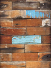 Wall Background Of Wooden Rectangles Of Different Brown Tones And Blue Brushstrokes. Grunge And Vintage Pattern. Peeling Paint Wooden Background.