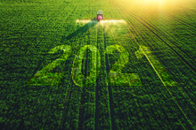 2021 Happy New Year Concept And Aerial View Of Farming Tractor Plowing And Spraying On Field.