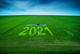 Fototapeta Kawa jest smaczna - 2021 Happy New Year concept and Aerial view of farming tractor plowing and spraying on field.