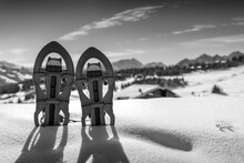 Black And White Photo Of Two Snowshoes Buried In The Snow With The Snowy Mountains In The Background