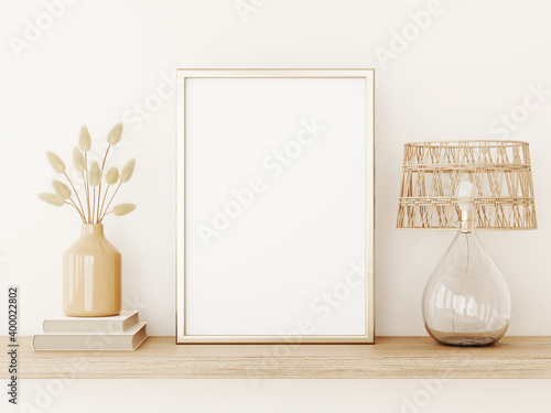Fotografía Vertical poster art mockup with gold metal frame, dried grass in vase, wicker lamp and books on empty warm beige wall background