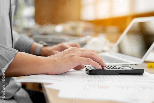 Cuadros en Lienzo Businessman pressing on calculator for calculating cost estimating with laptop