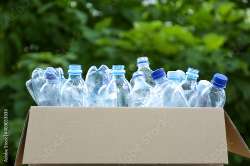 Obraz Cardboard box with used plastic bottles outdoors. Recycle concept - fototapety do salonu