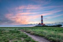 Closeup Shot Of A Lighthouse Near The Sea Under A Sunset Sky