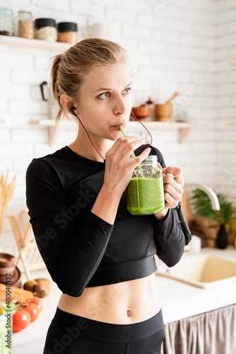 Obraz Young blond woman drinking green smoothie from mason jar at home kitchen - fototapety do salonu