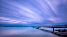 Long Exposure Shot Of A Deck Over The Sea Under A Purple Sky
