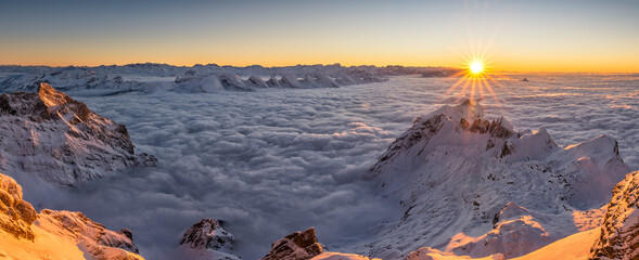 Panoramic shot of mountains covered in snow under a sunset sky