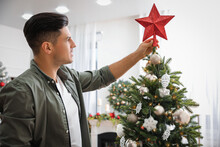 Man Decorating Christmas Tree With Star Topper Indoors