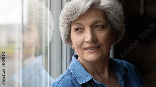 Head shot happy middle aged older hoary beautiful retired woman standing near window, dreaming alone indoors, visualizing future or planning holiday vacation, enjoying mindful moment at home Fotobehang