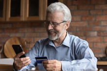 Smiling Mature Old Man In Glasses Enjoying Shopping In Internet Store Using Mobile Phone Applications, Satisfied With Fast Money Transfer Secure Service, Entering Payment Information From Credit Card.