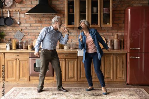 Obraz Happy older senior loving family couple having fun in kitchen, singing favorite karaoke songs in utensils. Positive joyful middle aged spouse enjoying funny domestic weekend activity together indoors. - fototapety do salonu