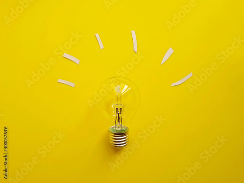 Closeup shot of a lightbulb isolated on yellow background. New idea concept, bright lightbulb idea