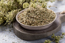 Bowl Of Dried Oregano Leaves On Stone Background.