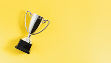 Winner Or Champion Silver Trophy Cup On Yellow Background Top View