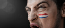 A Screaming Man With The Image Of The Country's National Flag On His Face