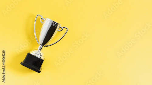 Fotografiet Winner or champion silver trophy cup on yellow background top view